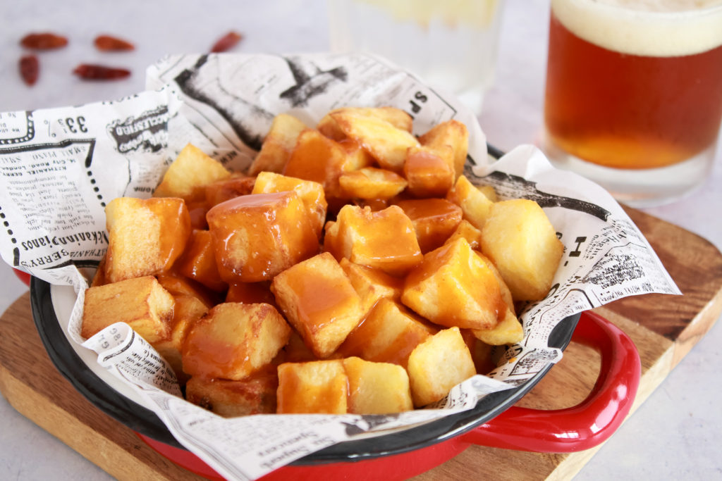 Patatas fritas en dados servidas con salsa brava