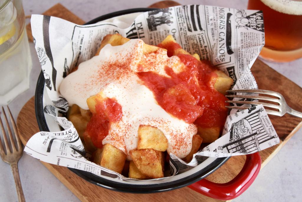 Patatas fritas en dados servidas con veganesa y salsa de tomate picante, decoradas con pimentón