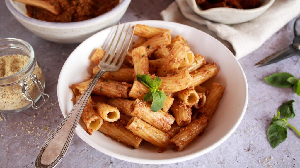Plato de pasta tortiglioni con pesto rosso y decorada con albahaca fresca
