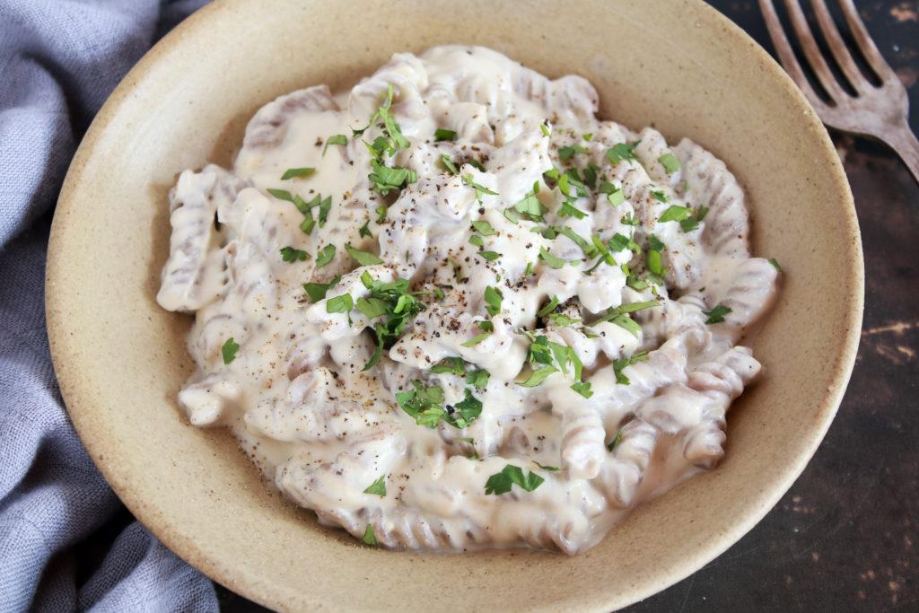 Plato de pasta fussilli con salsa Alfredo, blanca y decorada con perejil fresco picado