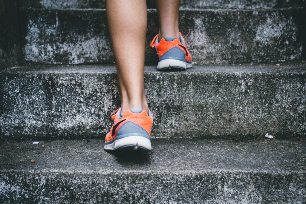 Pies con calzado deportivo en escaleras de piedra